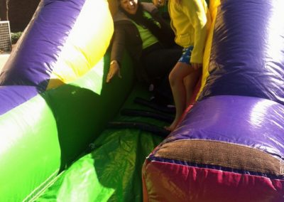 photo of child and adult climbing stairs of inflatable slide