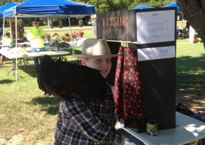 photo of boy holding a chicken at a kissing booth